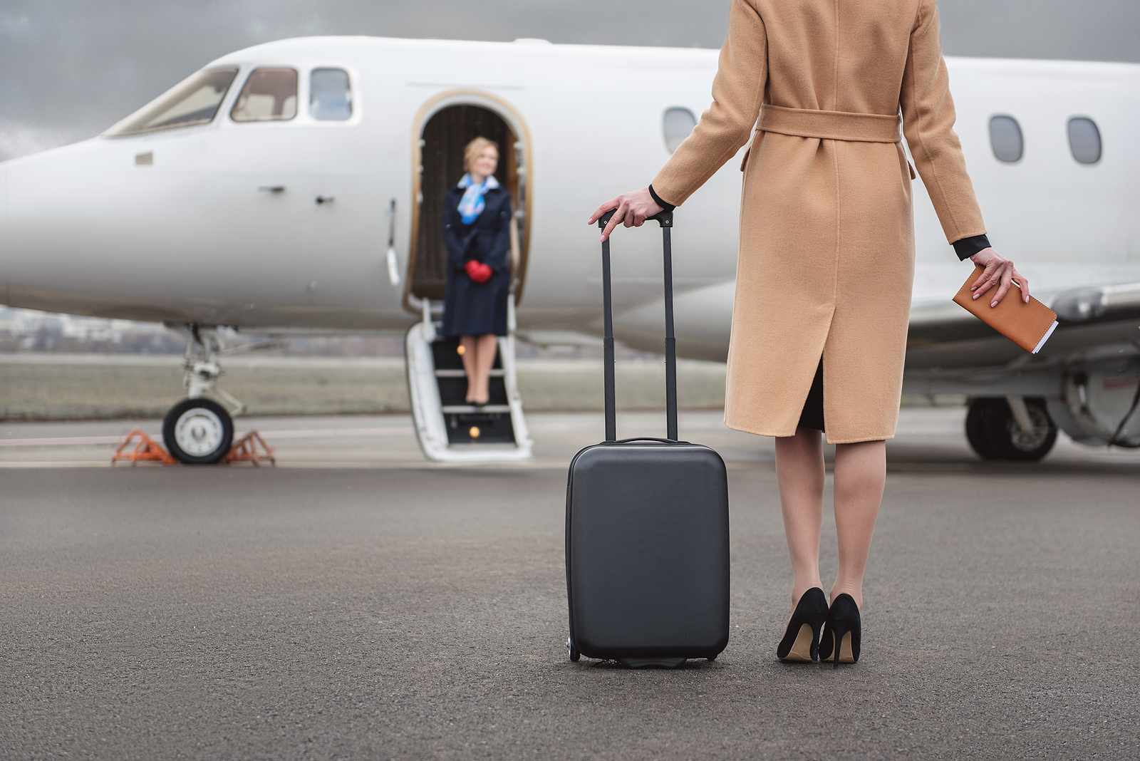 women with suitcase getting on private jet